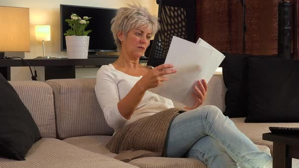 Thumbnail for A Serious Middle-aged Woman Sits on a Couch in an Apartment Living Room and Reads a Bunch of Papers
