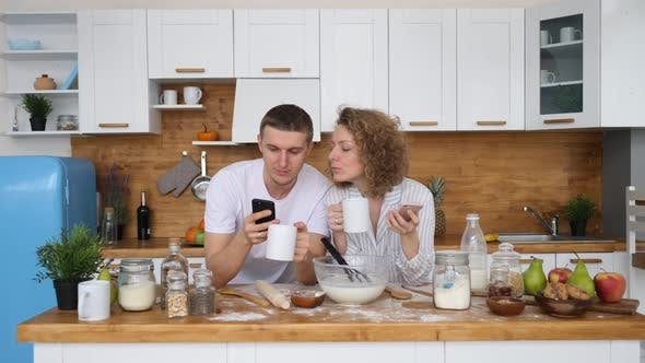Happy Couple Using Mobile Phones In Kitchen, People And Technology Concept