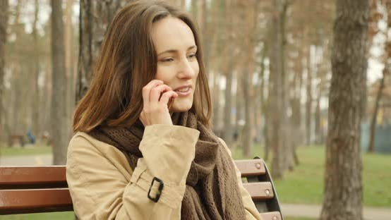 Thumbnail for Portrait of woman talking on phone sitting on bench in autumn park wearing brown scarf enjoy talking