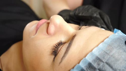 Professional Beautician Washes Female Eyes and Face Before Permanent Makeup Procedure