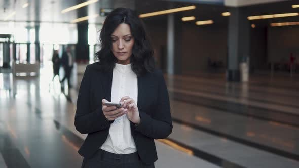 Thumbnail for a Woman in a Business Suit Walks Through the Lobby of a Modern Office Building. Business Woman Uses