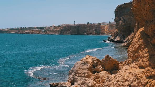 Thumbnail for Rocky Beach in Egypt. Beach in a Bay on the Coastline with Waves in the Blue Sea and Coral Reefs