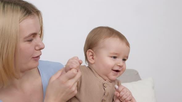 Entzückendes Baby schaut sich um und erkundet die Welt Mutter küsst kleine Hände