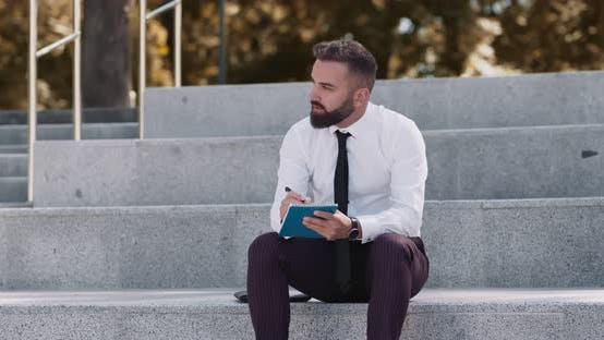 Thumbnail for Concentrated Businessman Creating Marketing Plan, Sitting on Stairs in Park