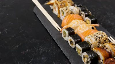 Rolls of Traditional Sushi on Black Stone Plate