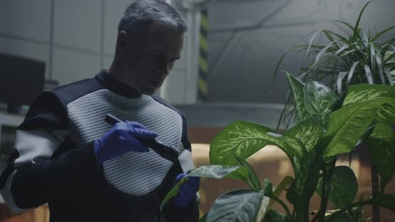Thumbnail for Scientist Examining Potted Plant in Mars Base