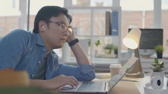 Thumbnail for Asian Office Worker Using Laptop and Falling Asleep