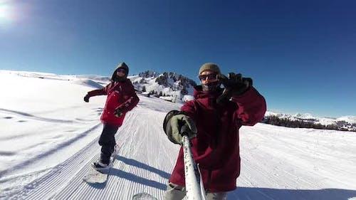 Men snowboarding down a mountain.