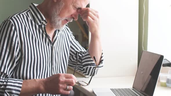 Thumbnail for Old Man at Home with Headache in Front of Laptop at Home