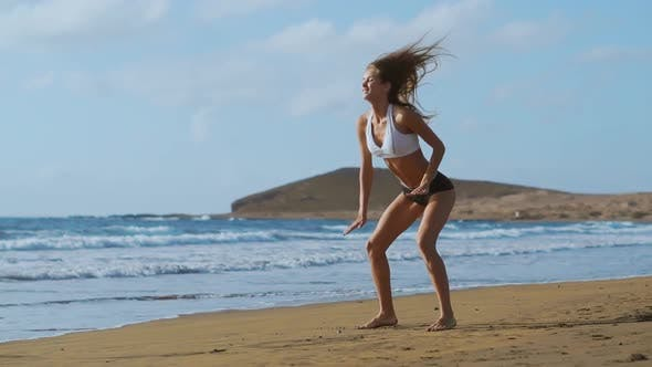 Thumbnail for Girl in Sportswear Shorts and T-shirt Performs Jumps with Squats and Claps on the Beach Near the