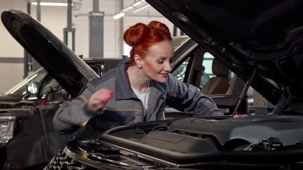 Thumbnail for Attractive Female Car Mechanic Examining Automobile with an Open Hood