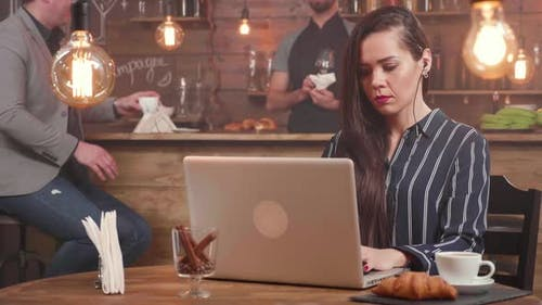 Young Female Freelance Writer Composing a Text at Her Laptop