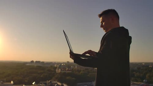 Programmer a Hacker Is on the Roof with a Laptop at Sunset Says Error Code on the Keyboard and