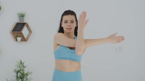 Active woman in blue sportswear  stretching arms and body doing exercises at home looking at camera