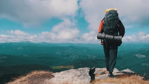 Thumbnail for Tourist with Backpack on the Top of Mountain Near the Cliff Raises Hands To Side