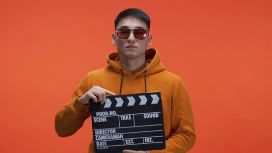 Thumbnail for Young Man Using Clapperboard