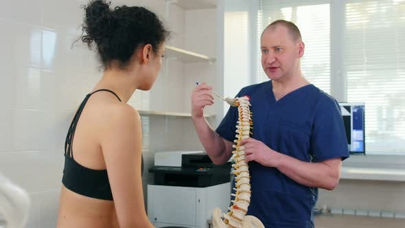 Thumbnail for Chiropractic Treatment - the Doctor Inspecting the Young Woman Before the Session - Showing the