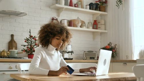 Lady Types on Keyboard Holding Credit Card and Buying Online