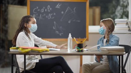 Junior High Students in Covid19 Face Masks Sitting at Desk in Classroom Talking