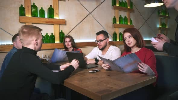 Waiter in Restaurant Takes Order From Group of Friends.