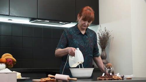 Frau mittleren Alters kocht in der modernen Küche und backt köstliches süßes Gebäck für die Familie.