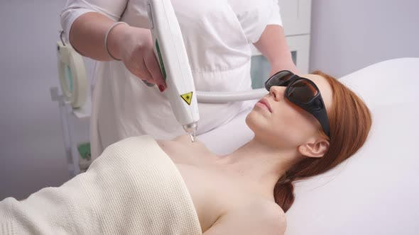 Young Woman Gets Laser Treatment of Her Cleavage By a Cosmetologist at a Beauty Clinic