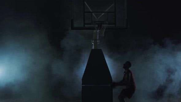 Thumbnail for Healthy Young Man Playing Basketball in Black Background with Clouds of Smoke