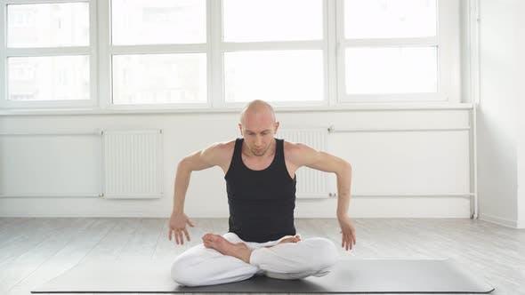 Professional Yoga Man Sits on Mat on Floor Training Correct Yoga Breathing