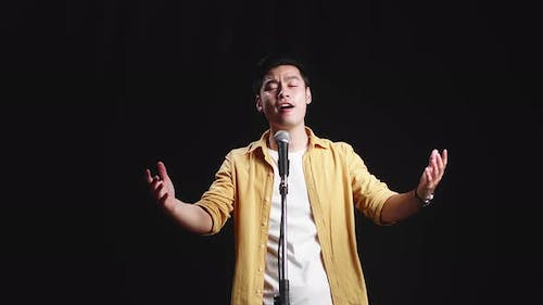 Asian Man Singer Singing Into Microphone On Black Background