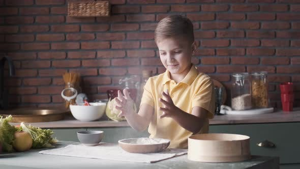 Thumbnail for Young Boy Is Clapping Hands in Flour Cooking in a Kitchen