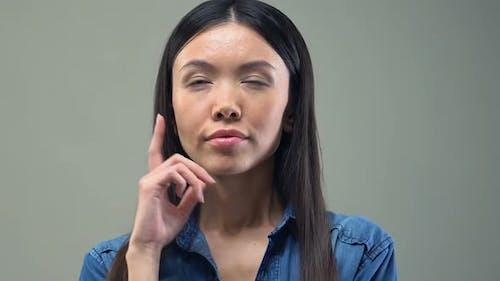 Pensive Asian Woman Touching Chin