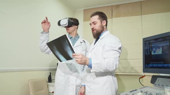 Thumbnail for Doctor Using 3d Vr Glasses, While His Colleague Examining X-ray of a Patient