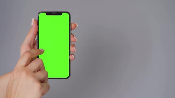 Thumbnail for Female Hands Using a Smartphone with a Green Screen on a Gray Background. Chroma Key.
