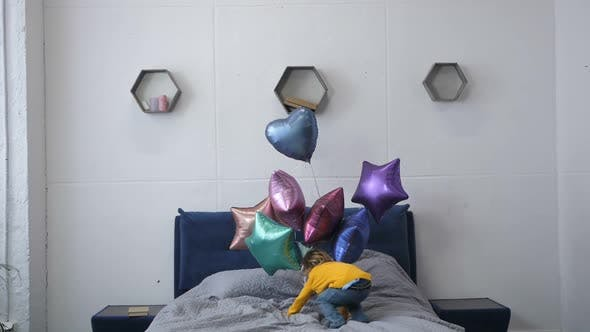 Thumbnail for Little Boy Jumping on Bed with Baloons
