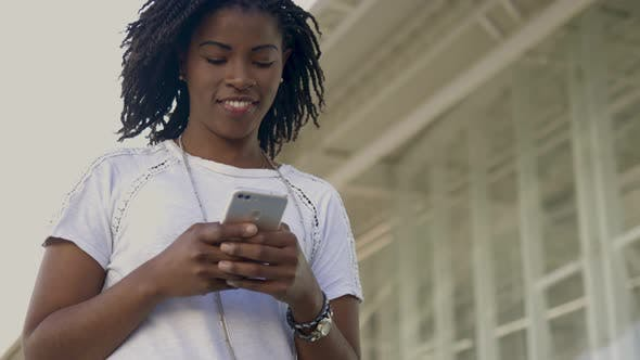 Thumbnail for Smiling African American Woman Using Smartphone During Stroll
