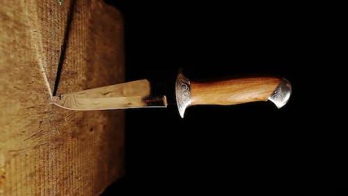 Scharfes Jagdmesser in einer Holzwand stecken