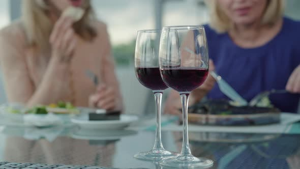 Thumbnail for Two Wineglasses with Drink Standing on the Table As Blurred Women Talking at the Background