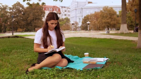 Thumbnail for Attractive Girl Reads Novel Outdoors