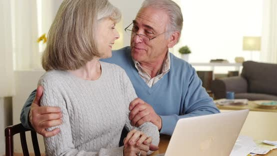 Happy senior couple using laptop computer to pay bills