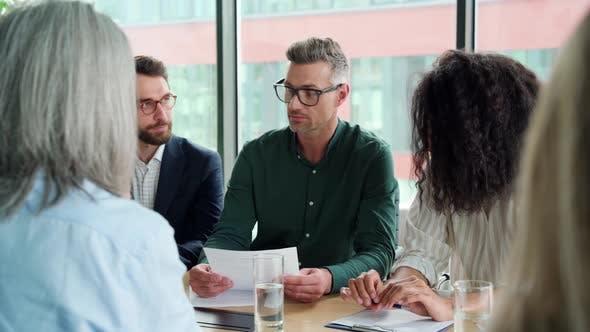 Businessman Handshaking Partner at Group Meeting Making Business Agreement