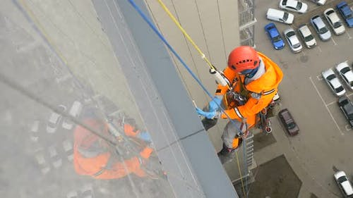 Industrial Climber Hangs on Tall Building and Puts Gloves for Working Fighting the Coronavirus