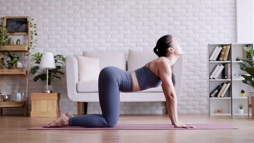 Asian woman practicing yoga pose Cat and Cow at home.