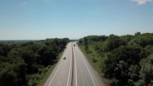 Aerial Shot of a Highway Passing Through the Rural Countryside and Green Forest