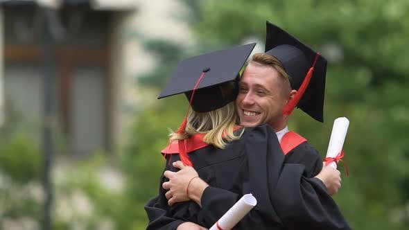 Thumbnail for Joyful Couple in Academic Dresses Hugging and Laughing, Happy Future, Education
