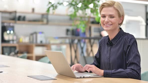 Thumbnail for Cheerful Young Businesswoman with Laptop Saying Yes By Head Shake