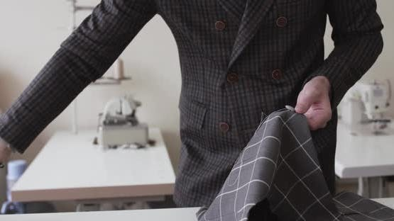 View of Tailor's Hands Stitching a Fabric Curve on a Desktop