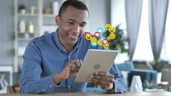 Thumbnail for Glückliche afrikanische Mann mit Tablet, Emojis, Smileys und Likes