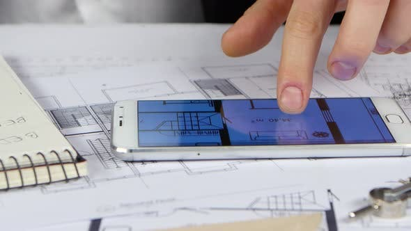 Thumbnail for Businessman Looks at Blueprints and Graphics in the Phone. Close Up