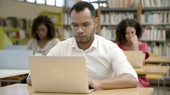 Front View of Focused African American Man Using Laptop at Library