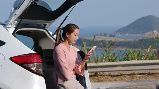 Thumbnail for Woman use of mobile phone for her road trip at countryside